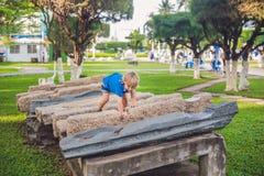 Netter blonder Junge klettert oben die Steinblöcke auf dem Spielplatz Kindheit, Konzept Stockbilder
