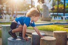 Netter blonder Junge klettert oben die Steinblöcke auf dem Spielplatz Kindheit, Konzept Lizenzfreie Stockfotos