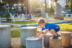Netter blonder Junge klettert oben die Steinblöcke auf dem Spielplatz Kindheit, Konzept Lizenzfreie Stockbilder