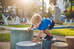 Netter blonder Junge klettert oben die Steinblöcke auf dem Spielplatz Kindheit, Konzept Stockfotos