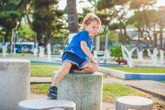Netter blonder Junge klettert oben die Steinblöcke auf dem Spielplatz Kindheit, Konzept Lizenzfreies Stockbild