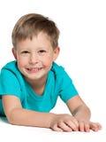 Netter blonder Junge liegt auf dem Weiß Stockfotos