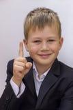 Netter blonder Junge mit einem angehobenen Finger oben Stockbilder