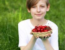 Netter blonder Junge mit einem Korb von Kirschen Stockfoto