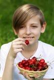 Netter blonder Junge mit einem Korb von Kirschen Stockbilder