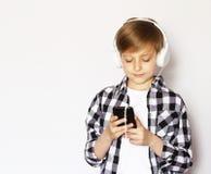 Netter blonder Junge mit einem Smartphone Lizenzfreies Stockbild