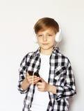 Netter blonder Junge mit einem Smartphone Lizenzfreie Stockfotografie