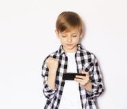 Netter blonder Junge mit einem Smartphone Lizenzfreie Stockfotos