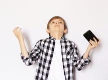 Netter blonder Junge mit einem Smartphone Lizenzfreies Stockfoto