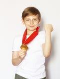 Netter blonder Junge mit Goldmedaille Stockbilder