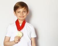 Netter blonder Junge mit Goldmedaille Stockbild