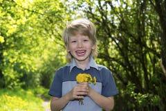 Netter blonder Junge mit Löwenzahn draußen Lizenzfreies Stockfoto