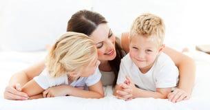 Netter blonder Junge mit seiner Schwester und seiner Mutter Stockfotografie
