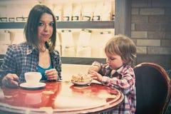 Netter netter blonder Junge mit Stück des Kuchens und seiner Mutter mit der Schale, die im Café sitzt Stockfotografie