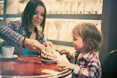 Netter netter blonder Junge mit Stück des Kuchens und seiner Mutter mit der Schale, die im Café sitzt Stockbilder
