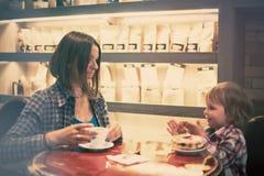 Netter netter blonder Junge mit Stück des Kuchens und seiner Mutter mit der Schale, die im Café sitzt Lizenzfreie Stockfotos