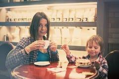 Netter netter blonder Junge mit Stück des Kuchens und seiner Mutter mit der Schale, die im Café sitzt Lizenzfreies Stockfoto