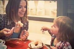 Netter netter blonder Junge mit Stück des Kuchens und seiner Mutter mit der Schale, die im Café sitzt Lizenzfreies Stockbild