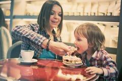 Netter netter blonder Junge mit Stück des Kuchens und seiner Mutter mit der Schale, die im Café sitzt Stockbild