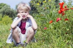 Netter blonder Junge sitzt auf dem Gebiet, Frühjahr Lizenzfreie Stockfotografie