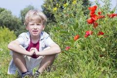 Netter blonder Junge sitzt auf dem Gebiet, Frühjahr Lizenzfreie Stockfotos