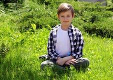 Netter blonder Junge sitzt auf dem Gras Lizenzfreies Stockfoto