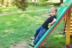 Netter blonder Junge am Spielplatz draußen Stockfotografie