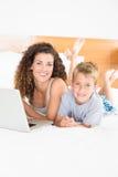 Netter blonder Junge und Mutter, die auf Bett unter Verwendung des Laptops liegt Stockfotografie