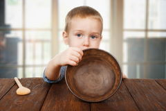 Netter blonder Junge zeigt leere Platte, Hungerkonzept Lizenzfreie Stockfotos
