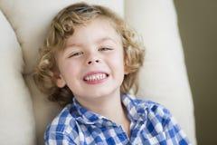 Netter blonder Jungen-lächelndes Sitzen im Stuhl Stockfotos