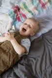 Netter blonder Jungenruf, der auf Bett liegt Lizenzfreie Stockfotografie