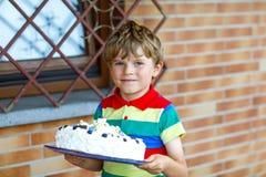 Netter blonder Kinderjunge, der großen Geburtstagskuchen hält Glückliches lächelndes Kind, das Geburtstag feiert Lizenzfreie Stockfotografie
