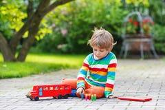 Netter blonder Kinderjunge, der mit rotem Schulbus und Spielwaren spielt Lizenzfreies Stockfoto