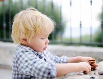 Netter blonder kleiner Junge, der draußen mit kleinen Steinen spielt Lizenzfreies Stockfoto
