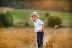Netter blonder kleiner Junge, der Spaß auf gelbem Heufeld hat Lizenzfreie Stockfotografie