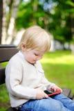 Netter blonder Kleinkindjunge, der draußen mit einer digitalen Tablette spielt Lizenzfreies Stockbild