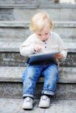 Netter blonder Kleinkindjunge, der draußen mit einer digitalen Tablette spielt Lizenzfreie Stockfotos