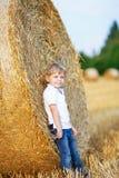 Netter blonder Kleinkindjunge, der Spaß auf Heufeld hat Stockfotos
