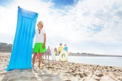Netter blonder lächelnder Junge mit matrass auf sandigem Strand Lizenzfreie Stockfotos