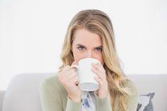 Netter blonder trinkender Kaffee, der auf angenehmem Sofa sitzt Stockfoto