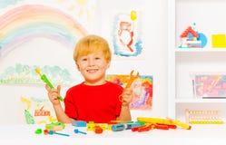 Netter blonder Vorschuljunge mit Spielzeugarbeitswerkzeugen Stockfoto