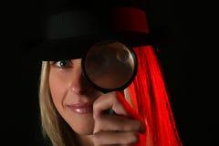 Netter blonder weiblicher Spion mit Vergrößerungsglas stockfotos