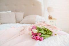 Netter Blumenstrauß mit den rosa und weißen Tulpen auf Bett Stockfoto
