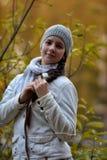 Netter Brunette in einer weißen Jacke und in einer grauen Kappe lizenzfreies stockbild