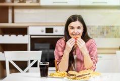 Netter Brunette genießt Hamburger stockfoto