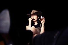 Netter Brunette mit einer Zigarre und einem Whisky in seiner Hand Stockbild