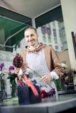 Netter Dekorateur, der seine Arbeit mit Blumen genießt lizenzfreie stockfotos