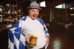Netter dicker Mann mit einem dicken Bauch mit einer oktoberfest Flagge und einem bayerischen Hut stockfotografie