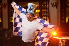 Netter dicker Mann mit einem dicken Bauch mit einer oktoberfest Flagge und einem bayerischen Hut stockfotos