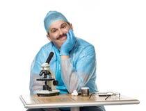 Netter Doktor mit Mikroskop Lizenzfreie Stockfotos